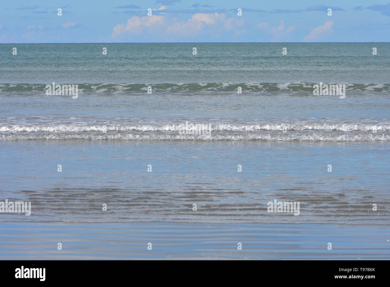 Rows of tiny surf waves coming from calm ocean to flat sandy beach. - Stock Image