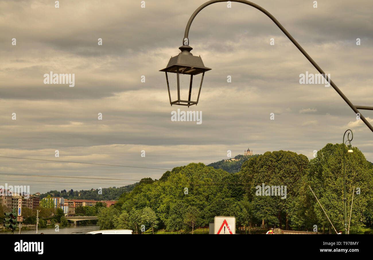 Turin, Piedmont, Italy. May 2019. The Basilica of Superga filmed by Piazza Vittorio. The green hills and a lamppost in the foreground are the setting - Stock Image