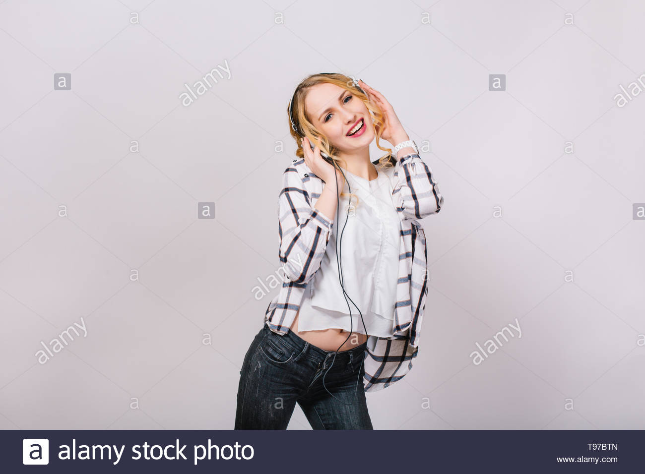 Stylish photo of mirthful attractive slim girl listening to favorite music and dancing near grey wall. Beautiful happy woman wearing casual plaid shirt and black jeans. Cheerful and satisfied. - Stock Image