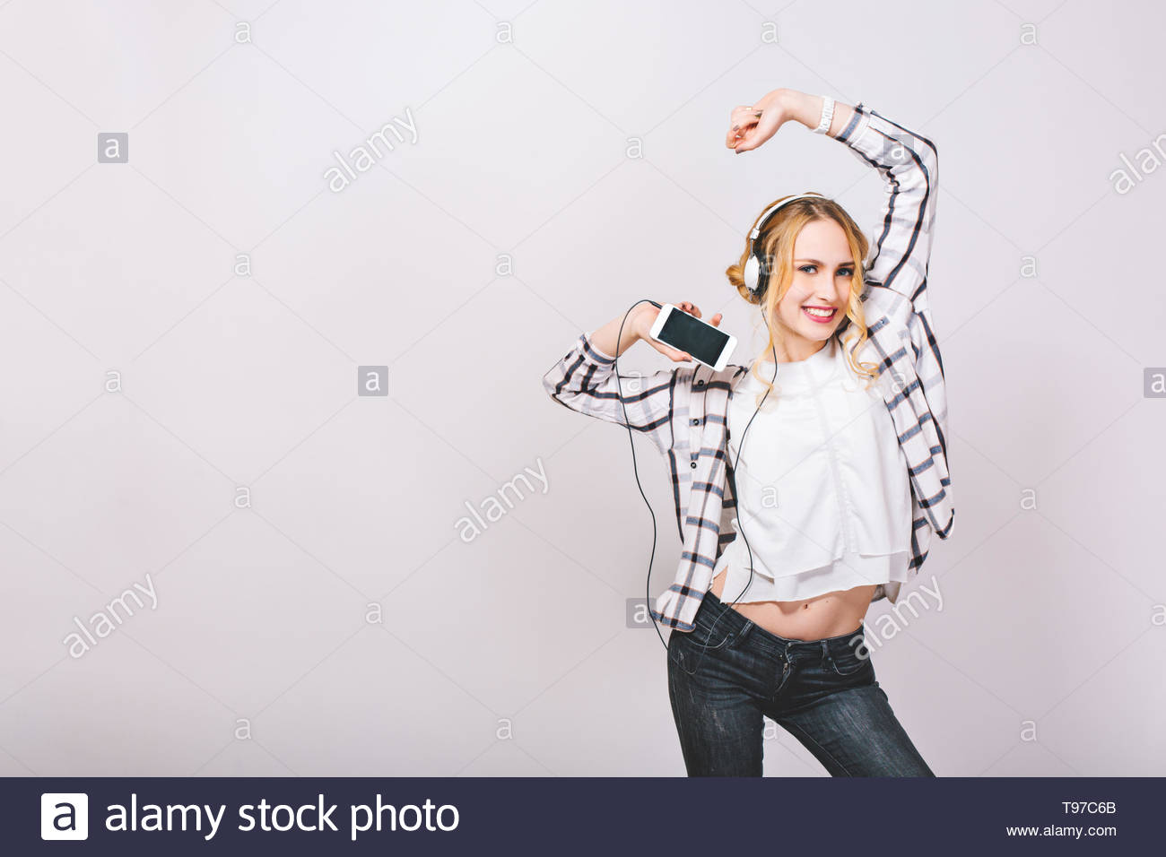 Positive photo emotional cute girl with smartphone, enjoying her life, listening to favorite music, dancing against grey wall. Leisure and technology concept. Good mood. - Stock Image