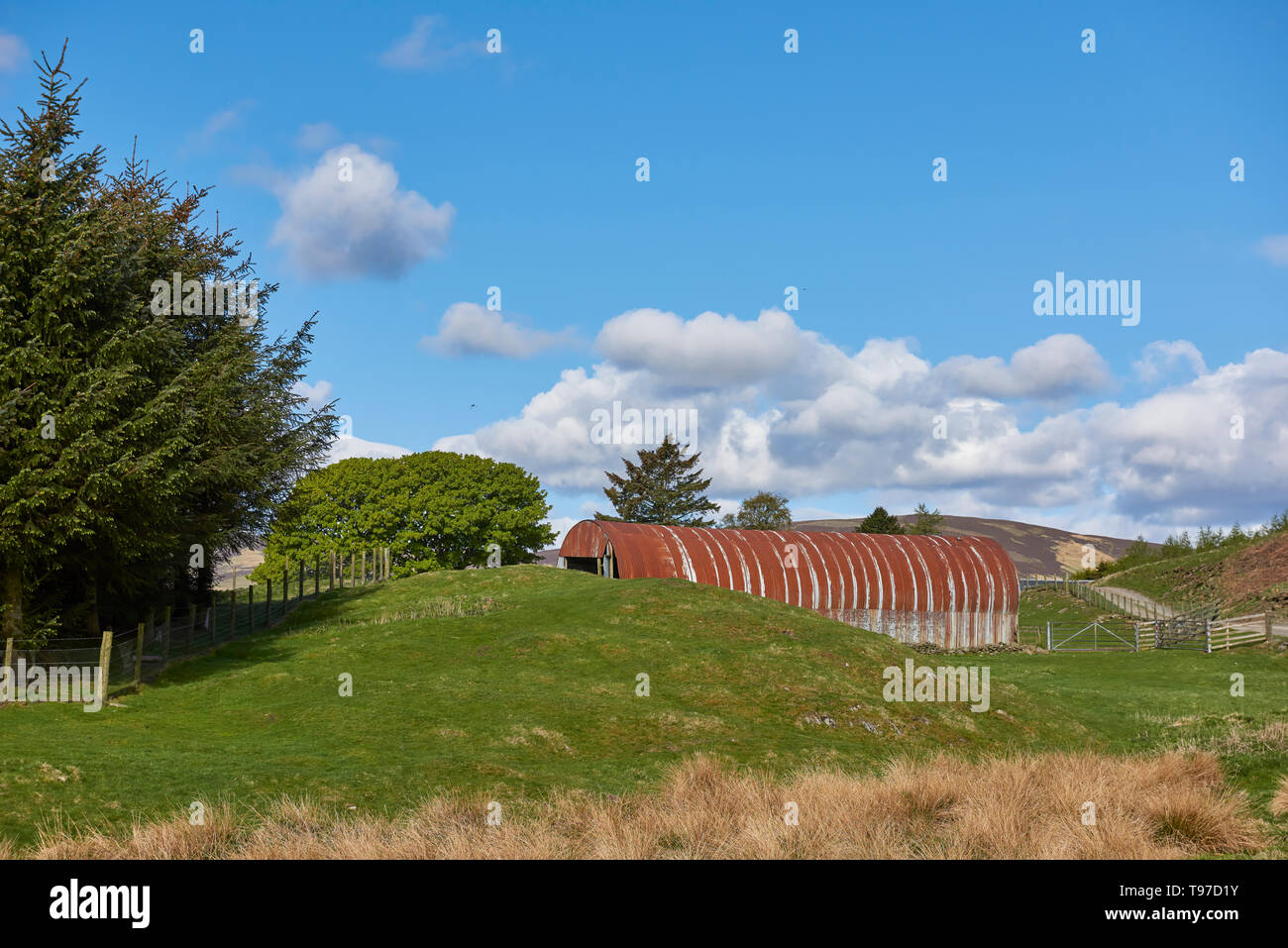 A Metal Nissan Hut styled Barn with Corrugated tin sides and a Roof on a small Hill Farm in the Angus Glens of Scotland. - Stock Image