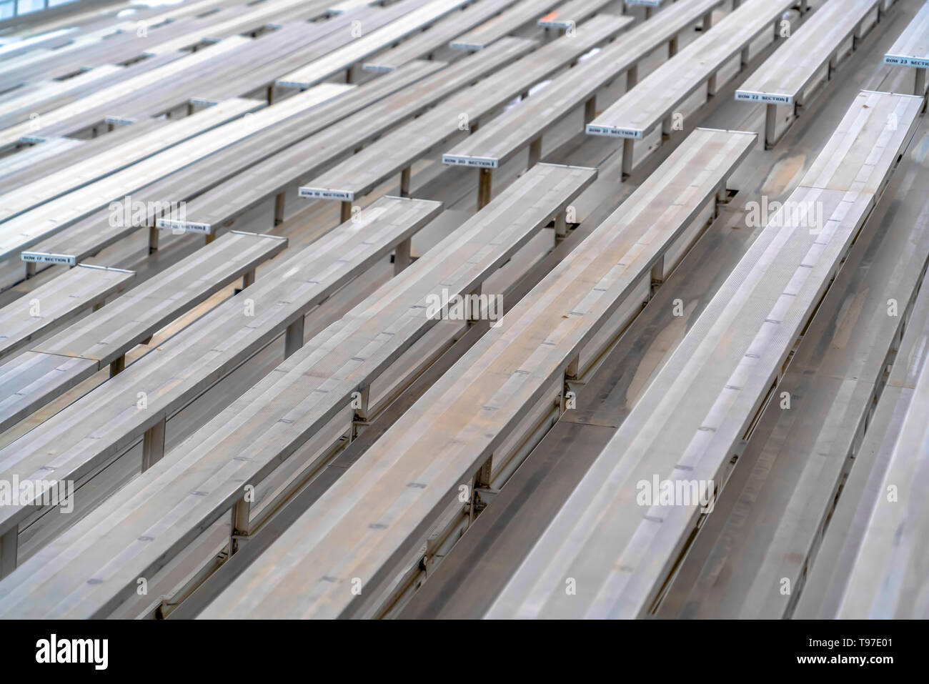 Close up of tiered rows of benches at a sports field viewed on a sunny day. - Stock Image