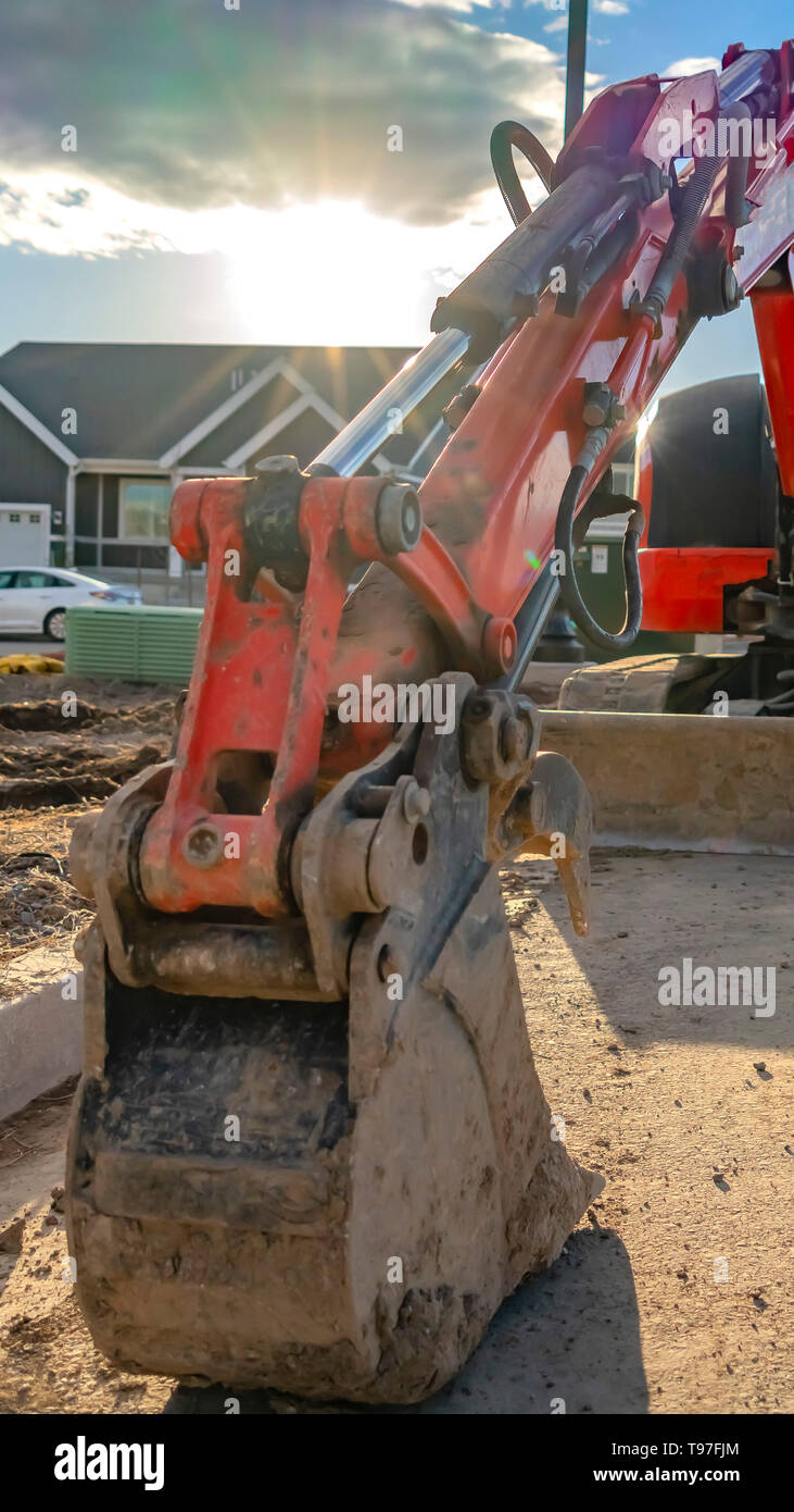 Clear Vertical Close up of a red excavator with an attched grader blade viewed on a sunny day - Stock Image