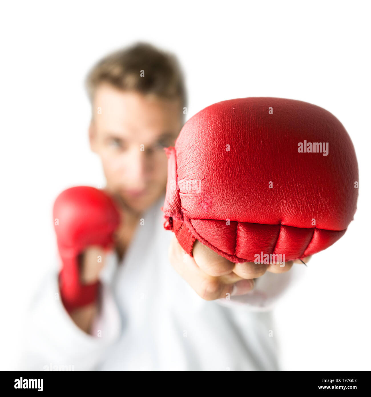 Kick boxer with red boxing gloves performing a martial arts punch. Isolated  over white background. - Stock Image