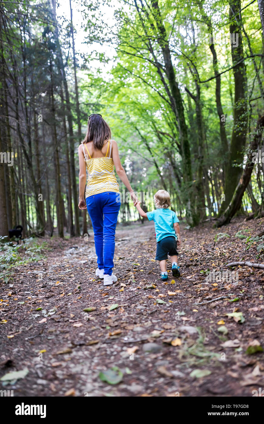 Rear view of young mother and her toddler son spending quality time together walking in the woods. - Stock Image