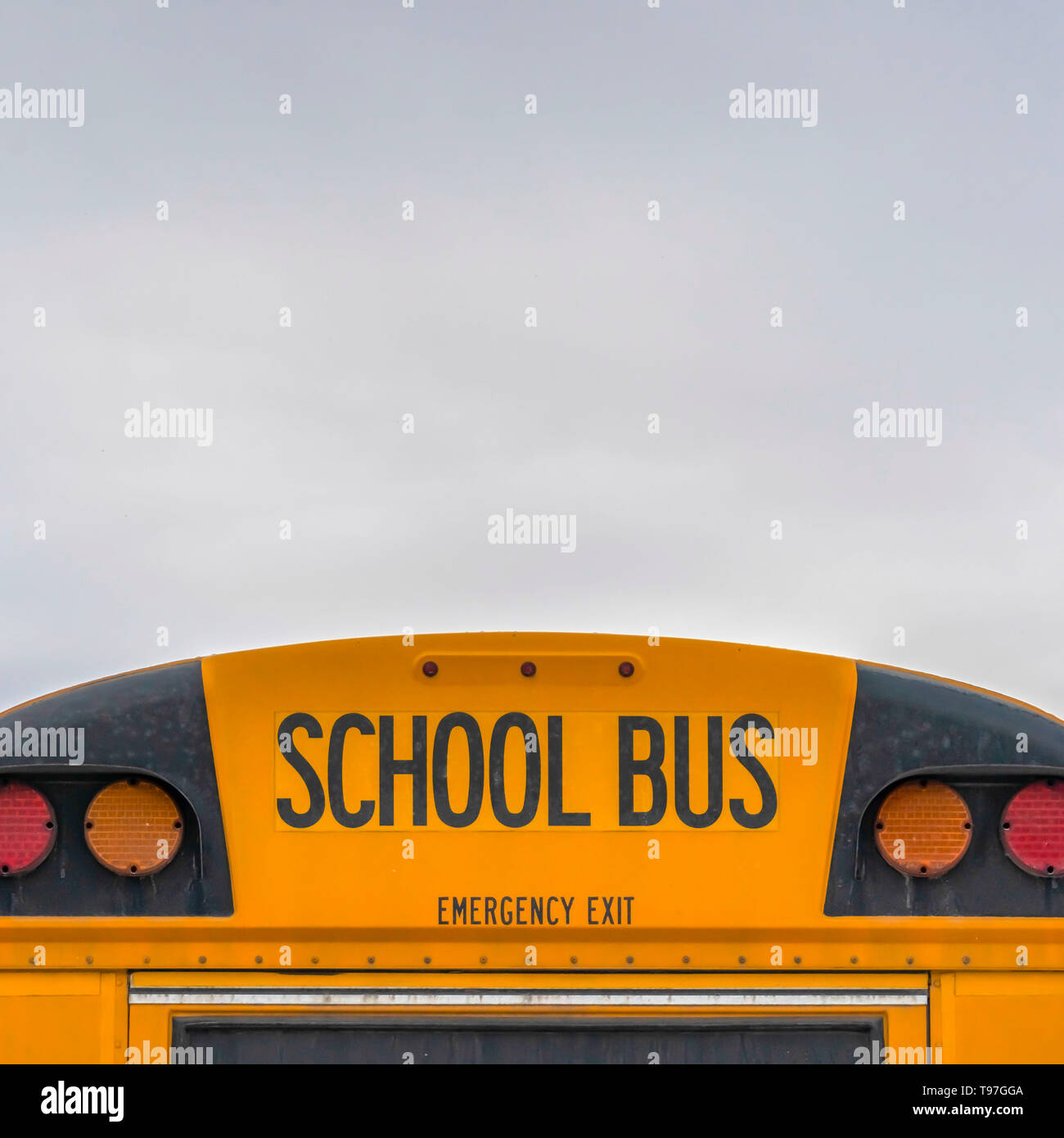 Square Rear of a yellow school bus with signal lights and emergency exit window - Stock Image