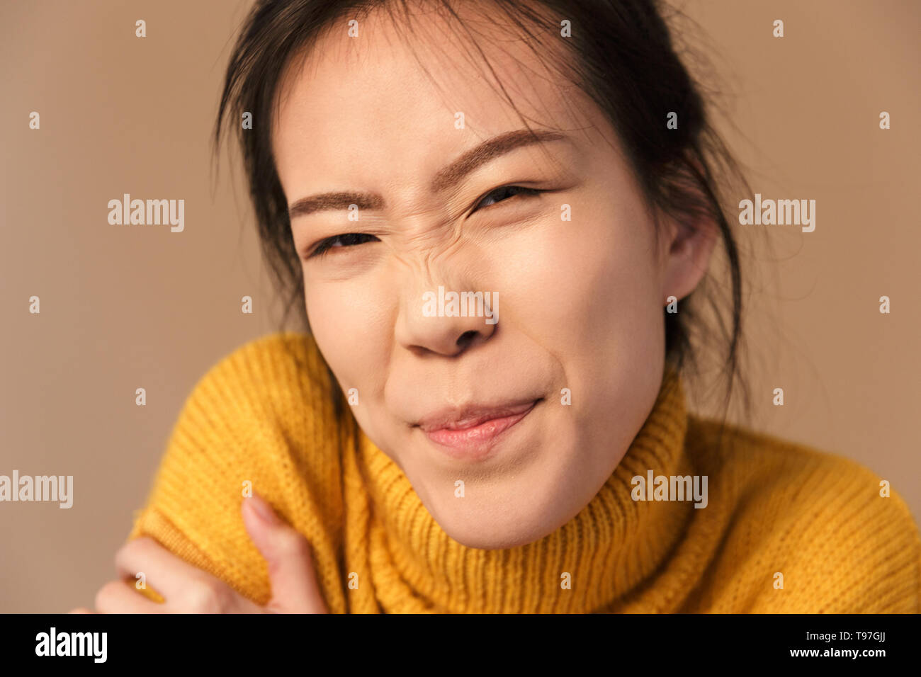Image closeup of funny asian woman wearing sweater grimacing while posing at camera in studio isolated over beige background - Stock Image