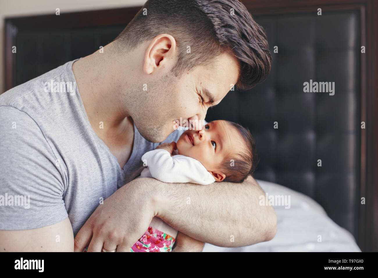 Closeup of young Caucasian father with newborn mixed race Asian Chinese baby. Male man parent holding child daughter son. Authentic lifestyle touching - Stock Image