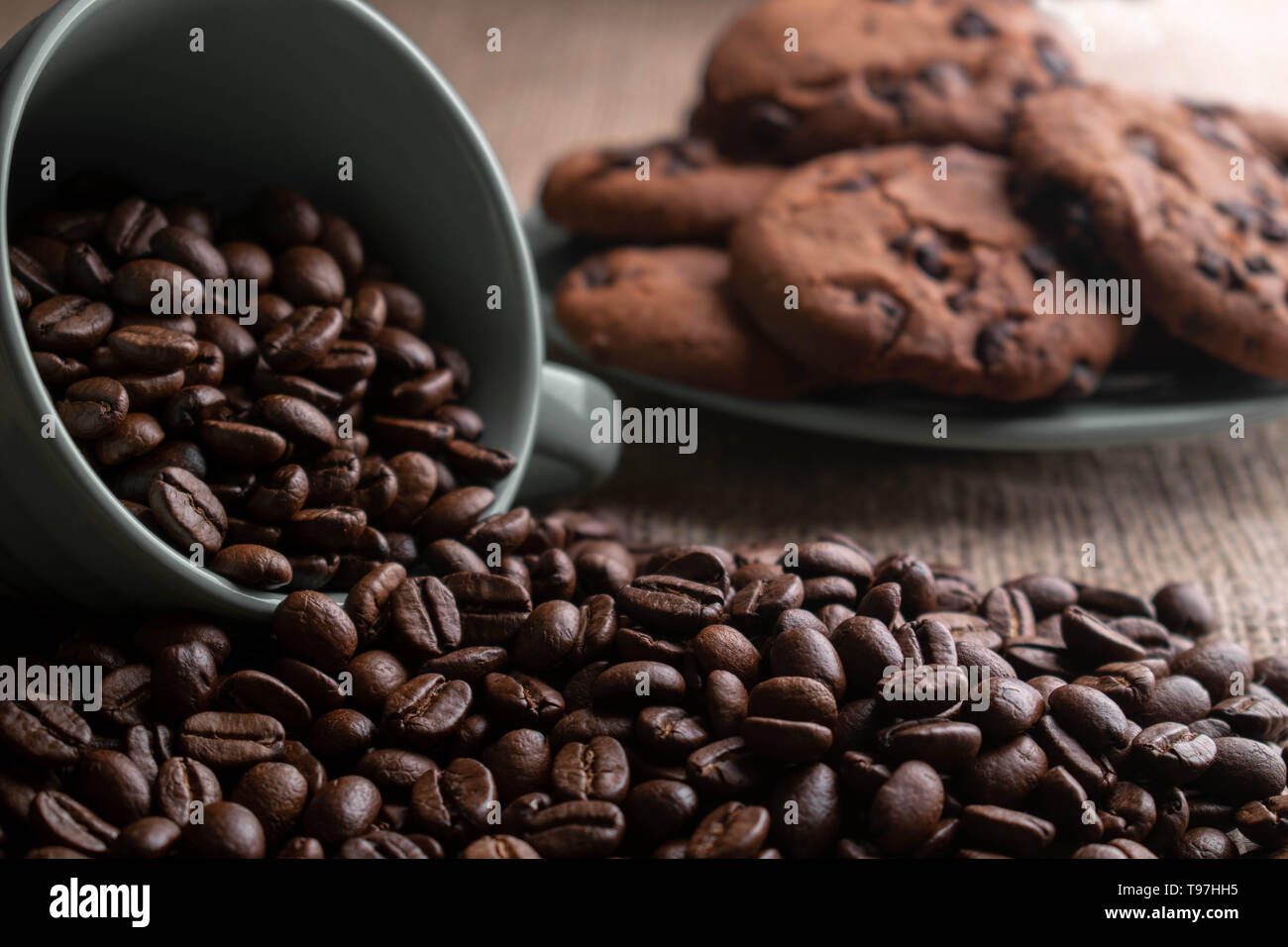 coffee beans crumbled with a cup which is worth on light burlap, in the background plate of cookies - Stock Image