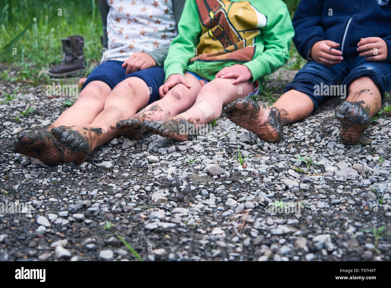 Three kids with bare and muddy feet sit on a pebble beach at the Russian River near Duncans Mills, California. - Stock Image