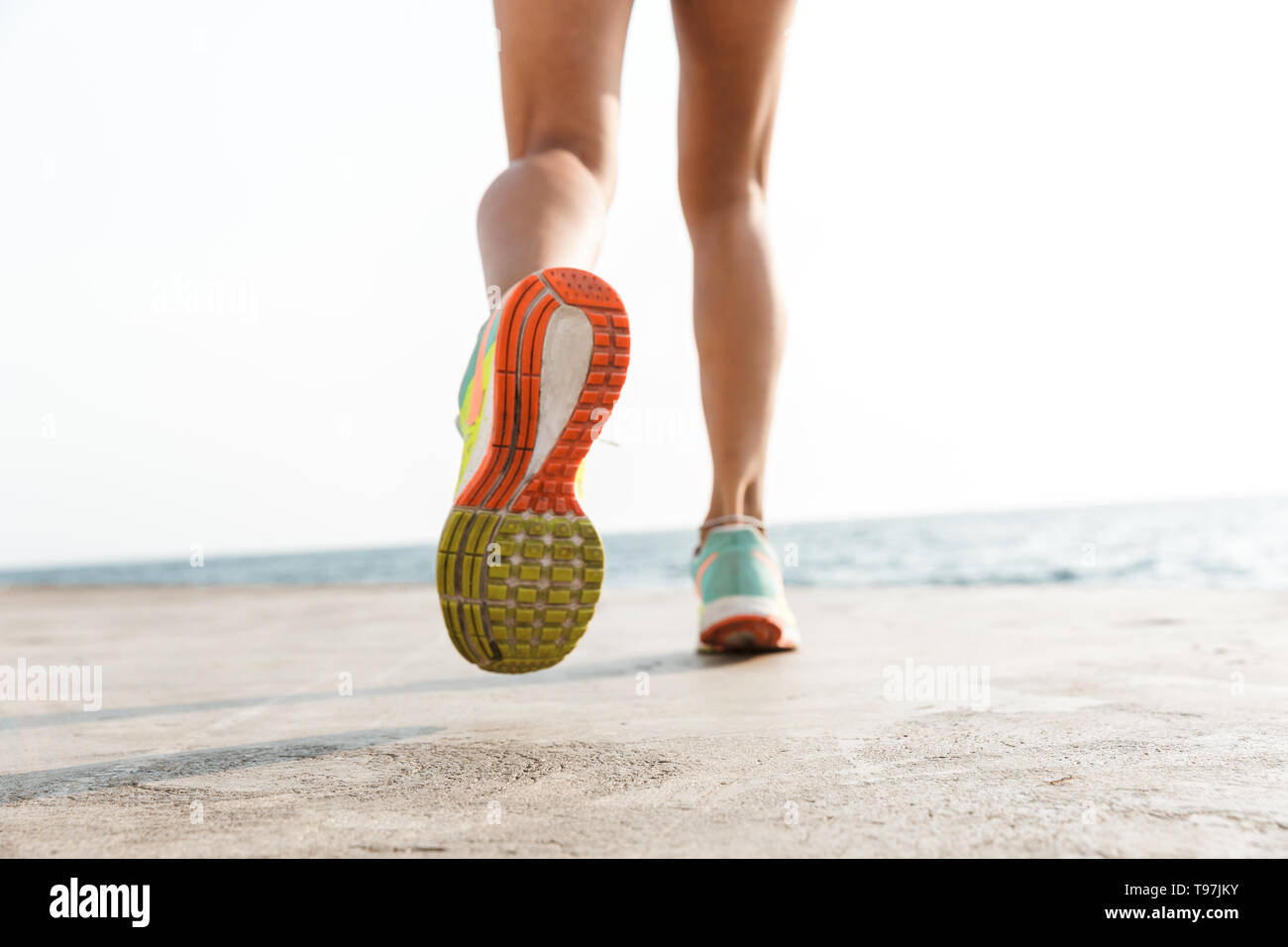 Back view of women's legs running along the beach - Stock Image