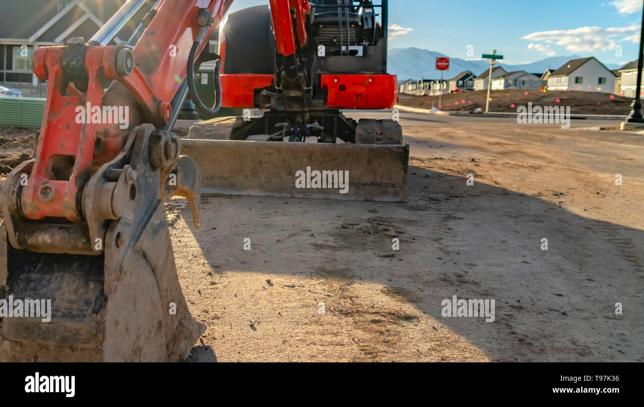 Panorama Close up of a red excavator with an attched grader blade viewed on a sunny day - Stock Image