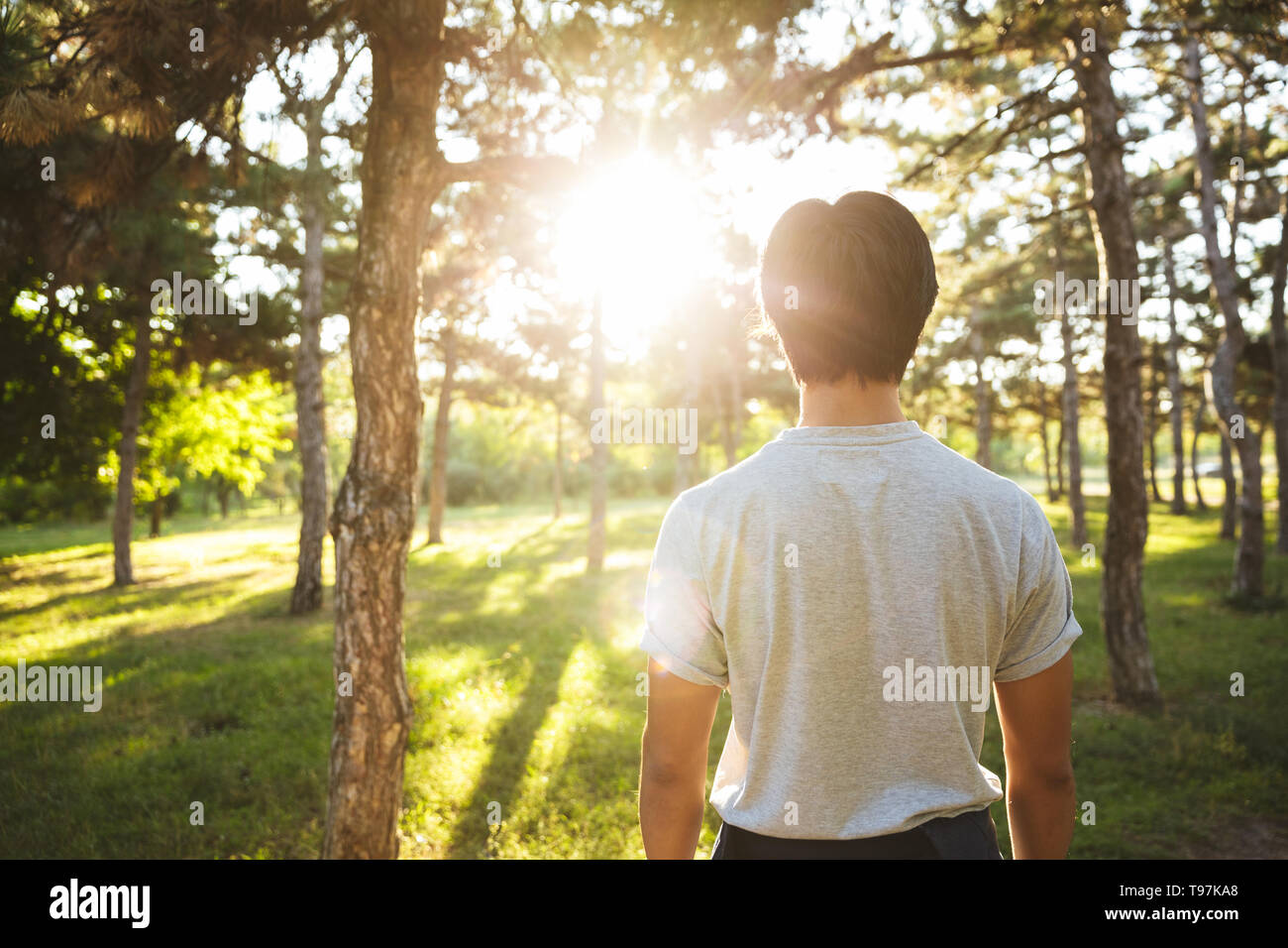 Back view of a young asian man wearing sportswear standing outdoors - Stock Image