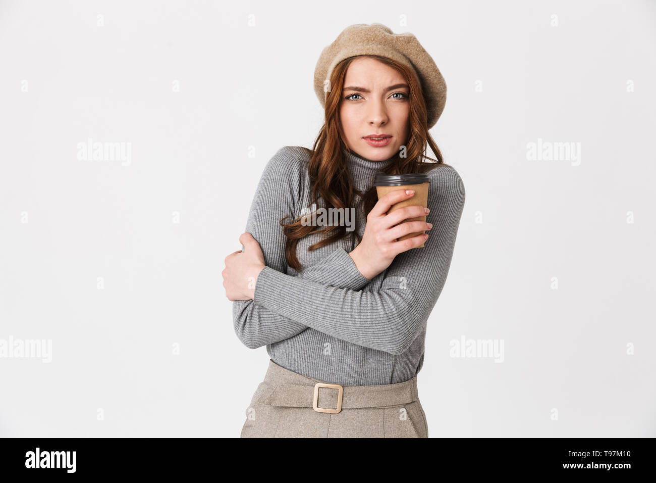 Image of beautiful frozen sad woman drinking coffee isolated over white wall background. - Stock Image
