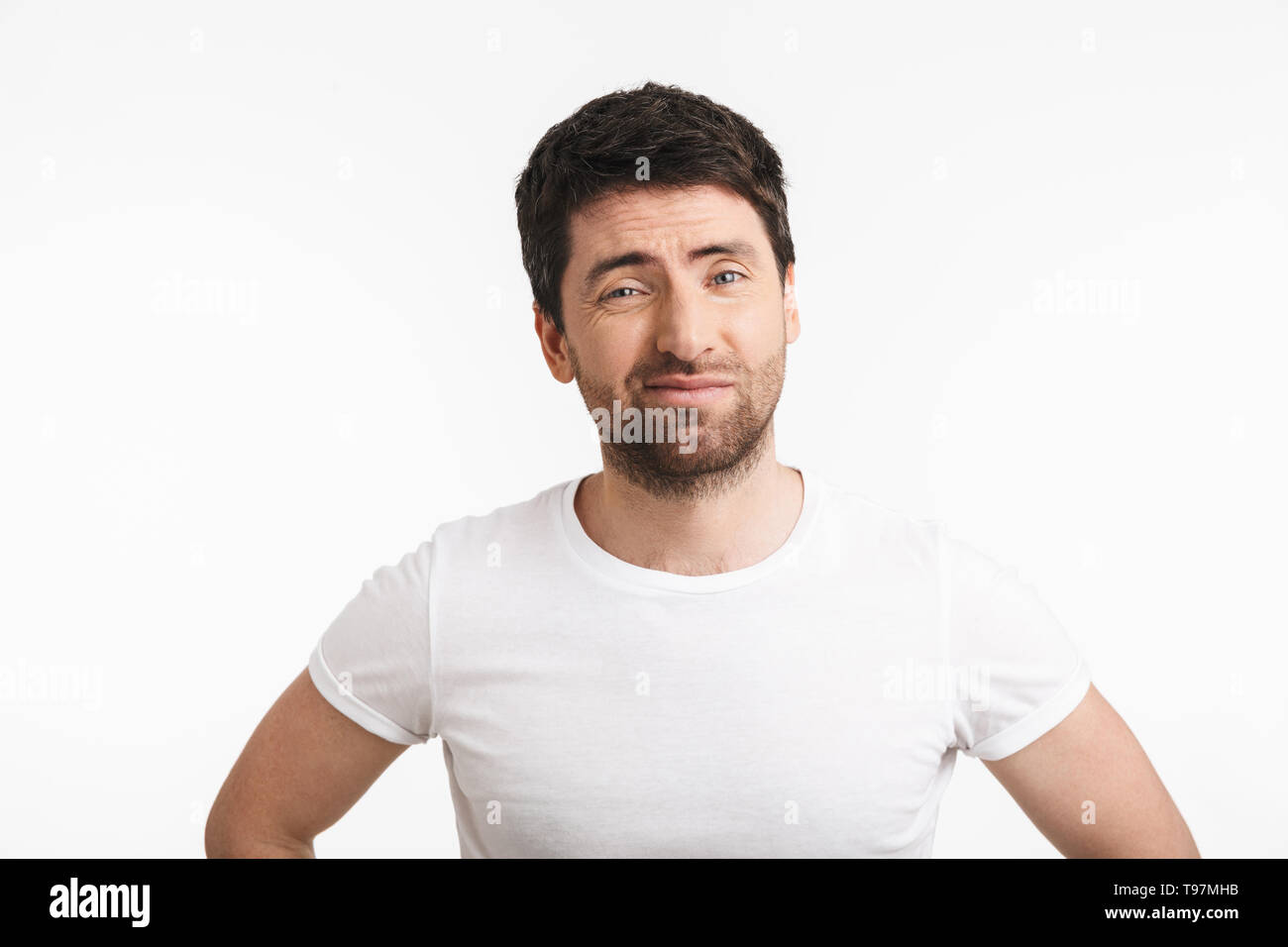 Image of unhappy man 30s with bristle in casual t-shirt frowning and grimacing isolated over white background - Stock Image