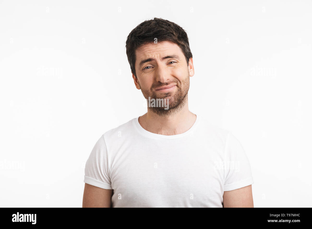Image of unsure man 30s with bristle in casual t-shirt frowning and grimacing isolated over white background - Stock Image