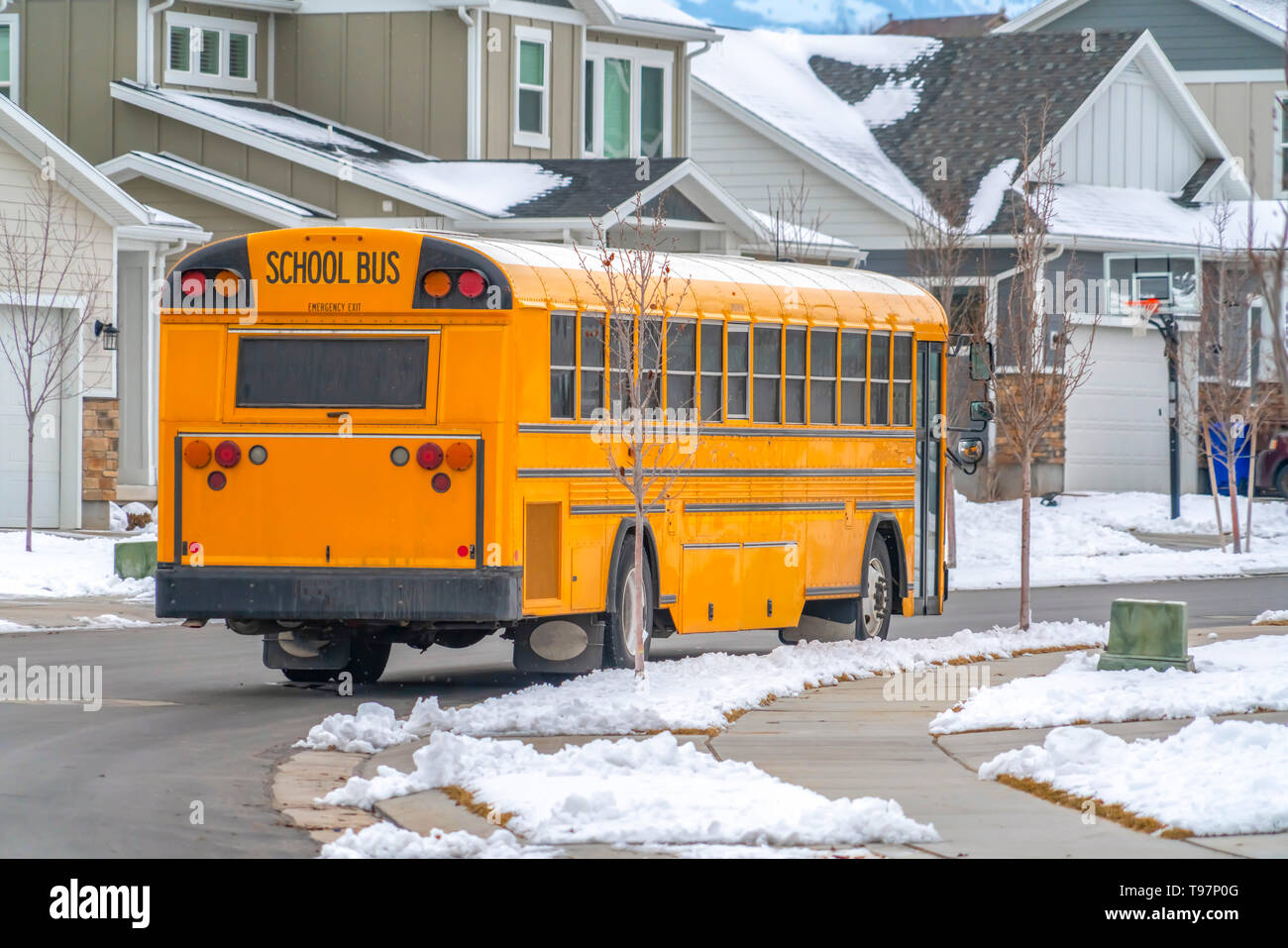 Rear view of a yellow school bus running on a road with fresh snow in winter - Stock Image