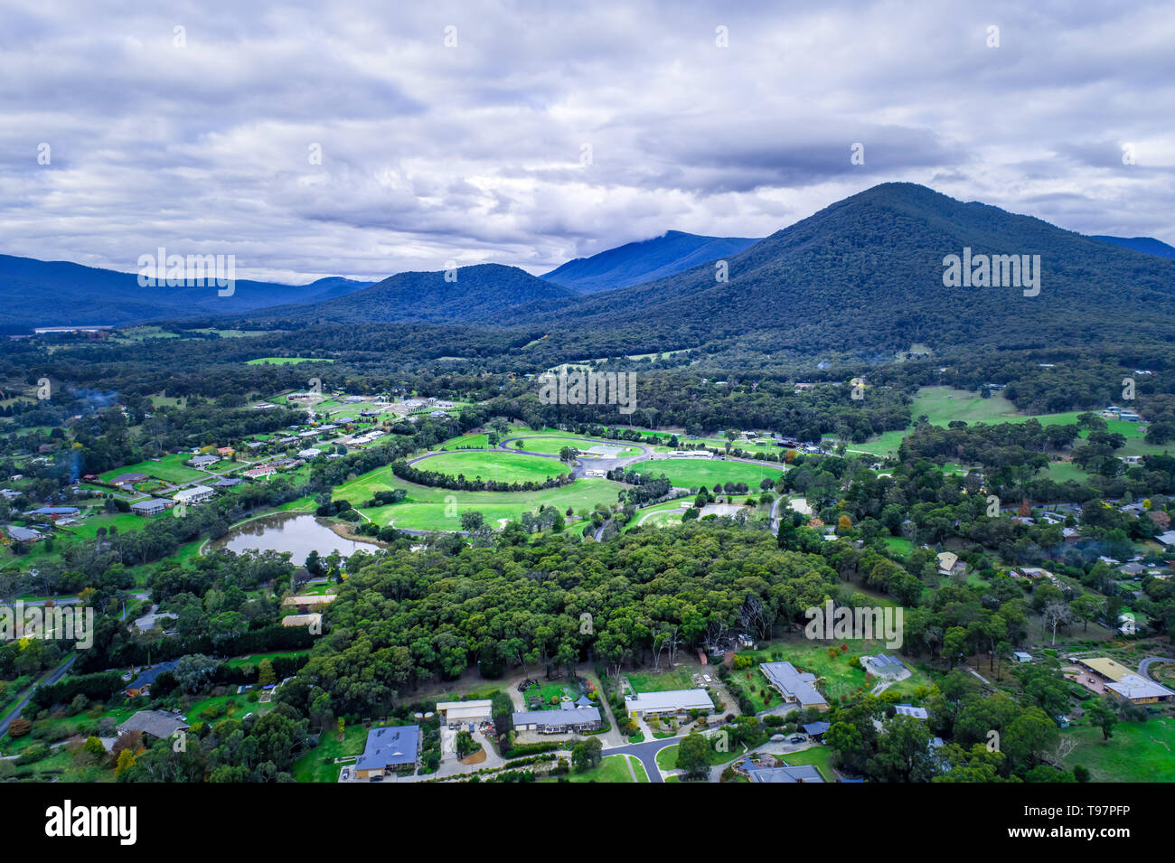 Scenic rural landscape of houses among grasslands with trees and mountains. Healesville, Victoria, Australia - Stock Image