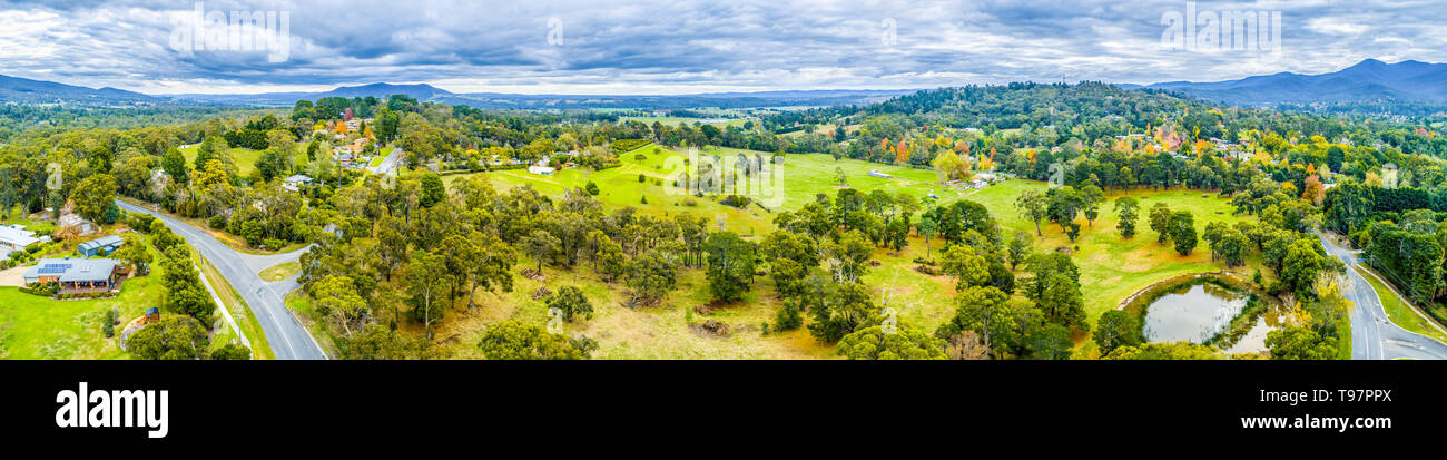 Wide aerial panoramic landscape of scenic countryside. Grasslands among trees and mountains in Australia - Stock Image