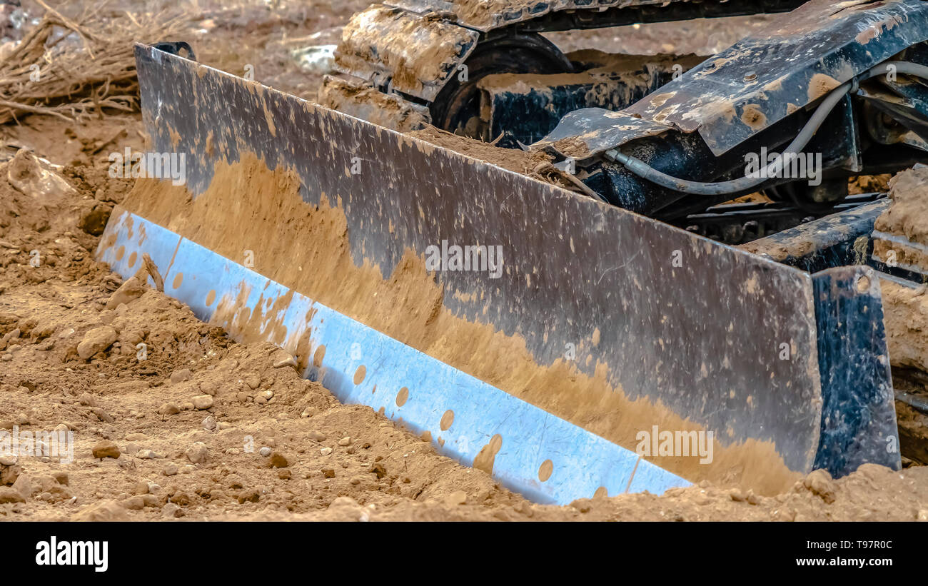 Close up of a metal grader blade against the ground with brown soil - Stock Image