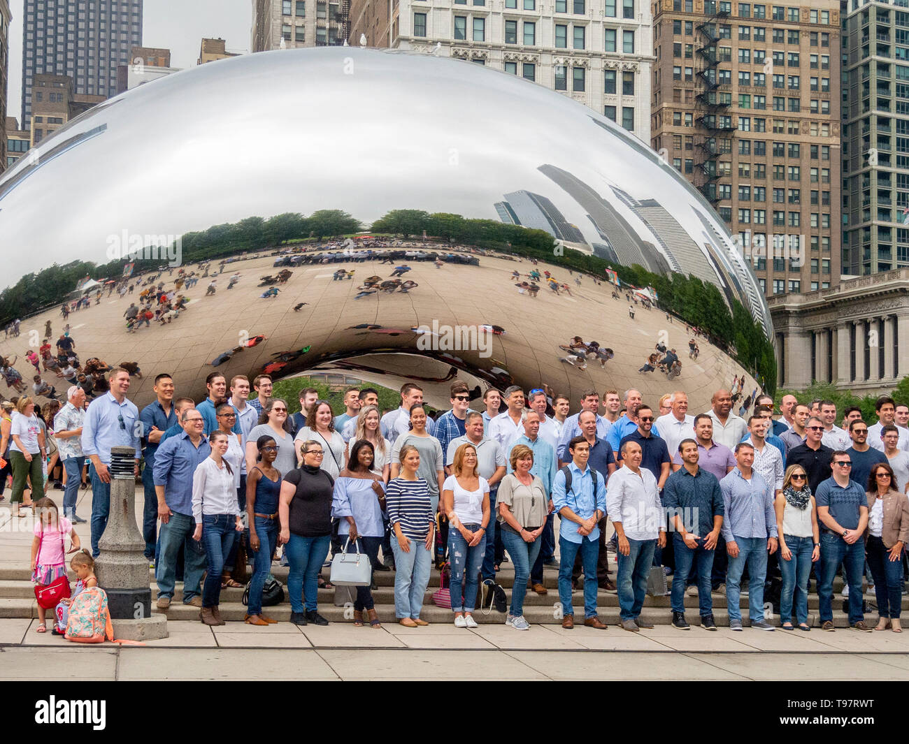 Tourists pose for a group photo at Cloud Gate in Millenium Park, Chicago. Cloud Gate is a public sculpture by Indian-born British artist Sir Anish Kapoor, that is the centerpiece of AT&T Plaza at Millennium Park in the Loop community area. - Stock Image