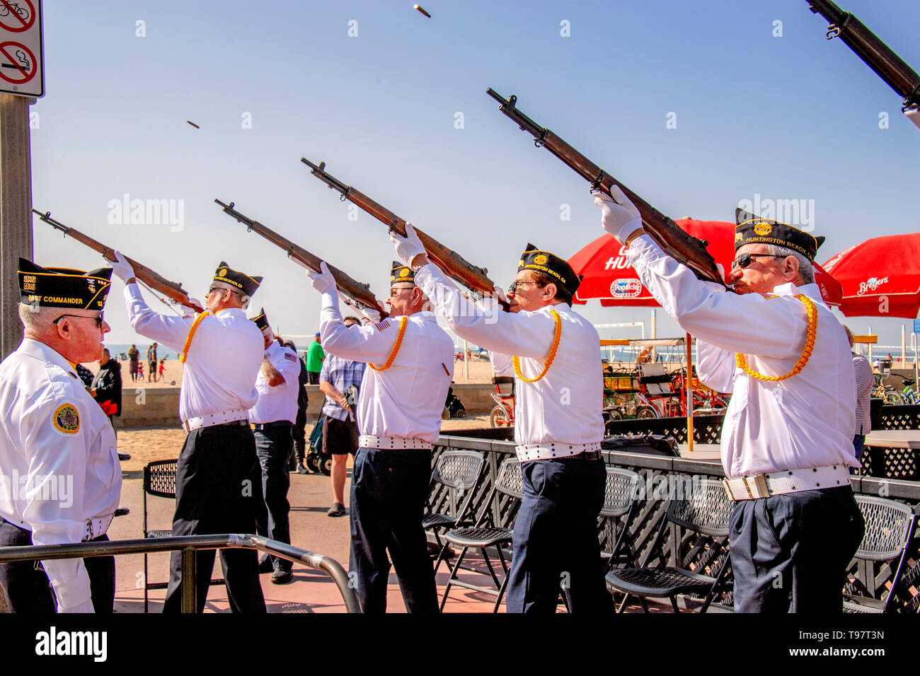Cartridge cases fly as an American Legion Honor Guard fires a three volley rifle salute at Veterans Day ceremonies in Huntington Beach, CA. - Stock Image