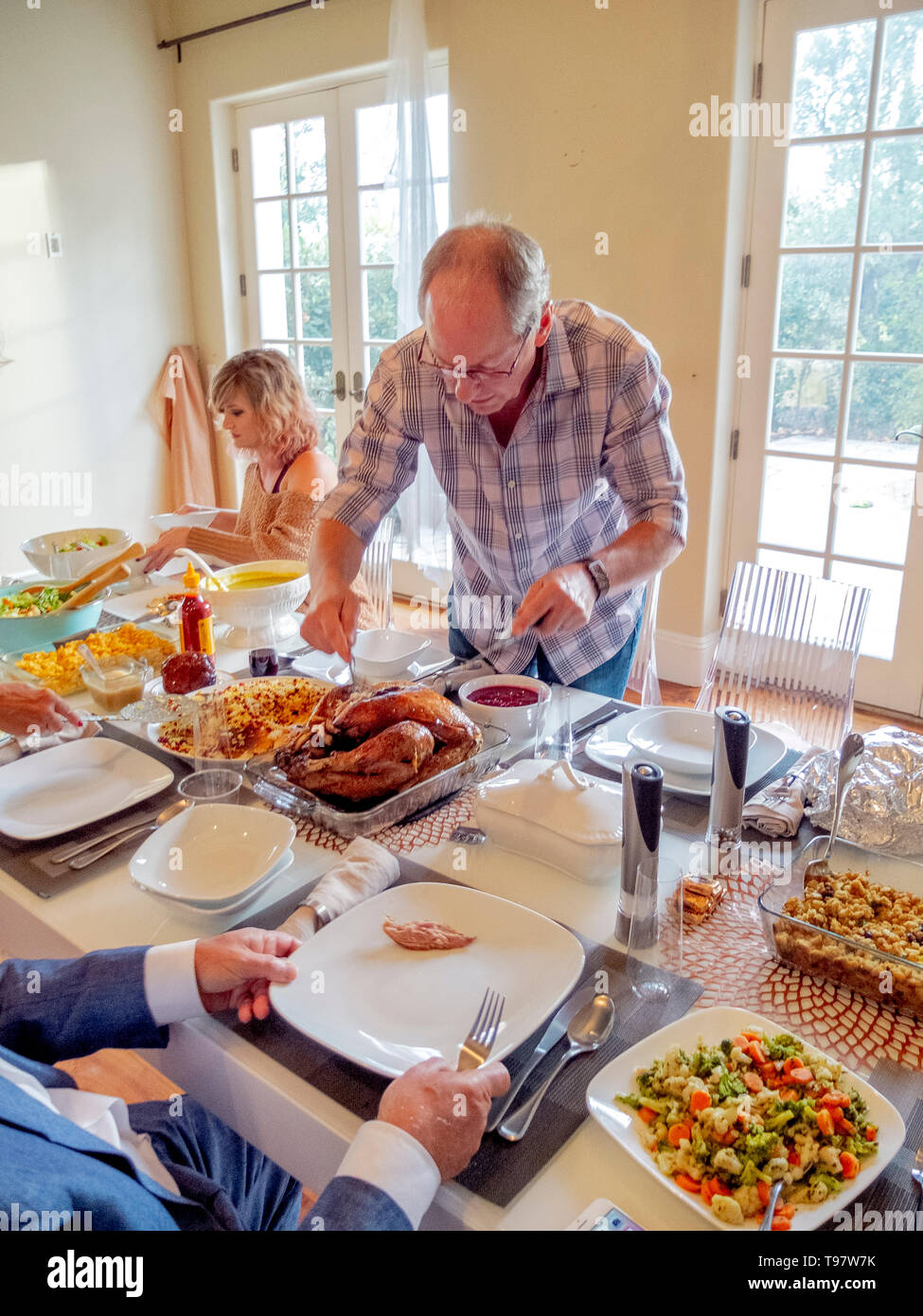 Accompanied by his daughter, a Caucasian senior man carves a Thanksgiving turkey during a holiday meal at home in San Juan Capistrano, CA. - Stock Image