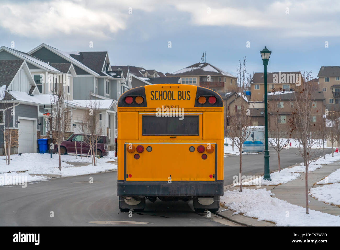Rear view of a yellow school bus with a window and several signal lights - Stock Image