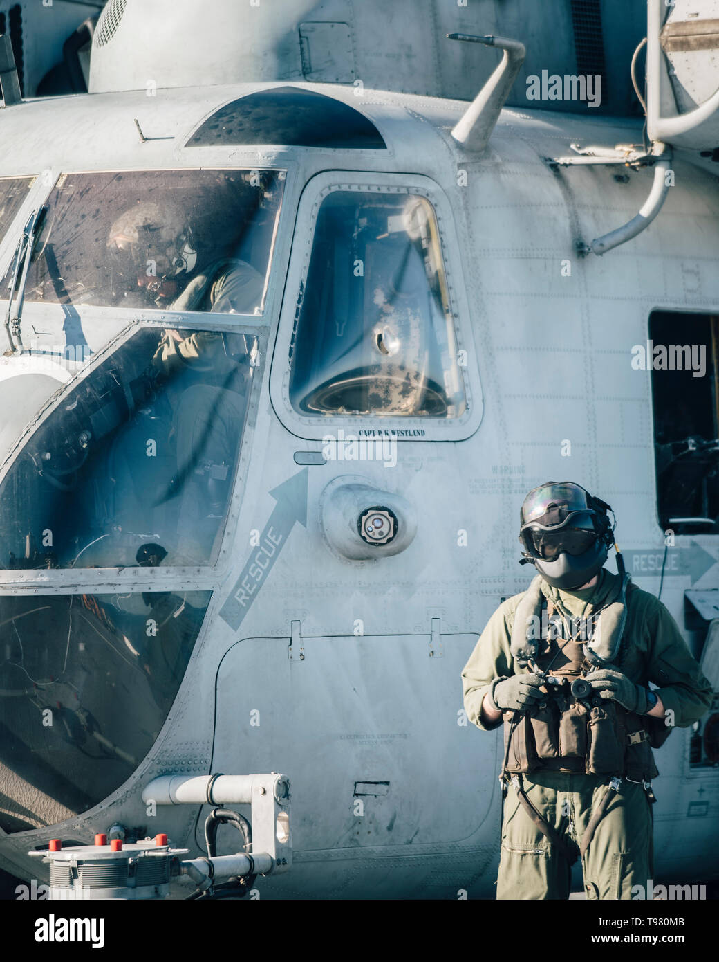 190511-M-HB658-0028 PACIFIC OCEAN (May 11, 2019) A U.S. Marine Corps CH-53E Super Stallion crew chief with Marine Medium Tiltrotor Squadron (VMM) 163 (Reinforced), 11th Marine Expeditionary Unit (MEU), stands beside an aircraft aboard the San Antonio-class amphibious transport dock ship USS John P. Murtha (LPD 26). The Marines and Sailors of the 11th MEU are conducting routine operations as part of the Boxer Amphibious Ready Group. (U.S. Marine Corps photo by Staff Sgt. Donald Holbert) - Stock Image