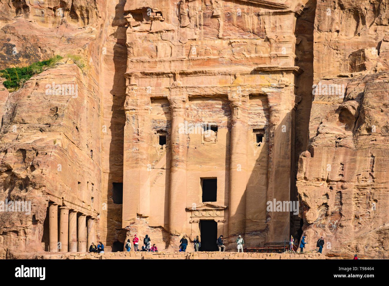Some tourists are admiring and taking pictures of a huge temple carved into the rock. Stock Photo