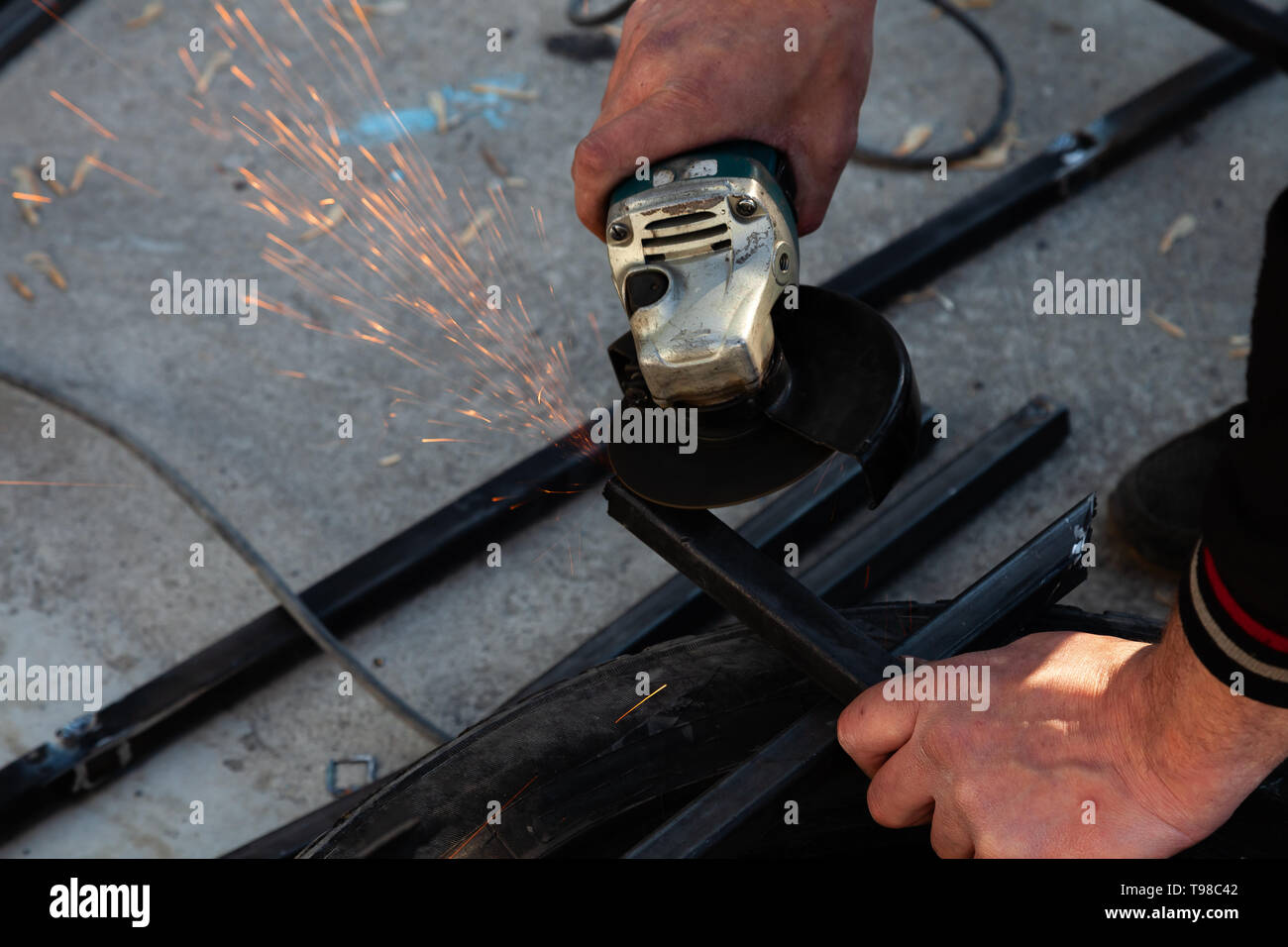Close-up view strong man master without gloves on arms, performs metal cutting with an angle grinder in the garage workshop, blue and orange sparks fl - Stock Image