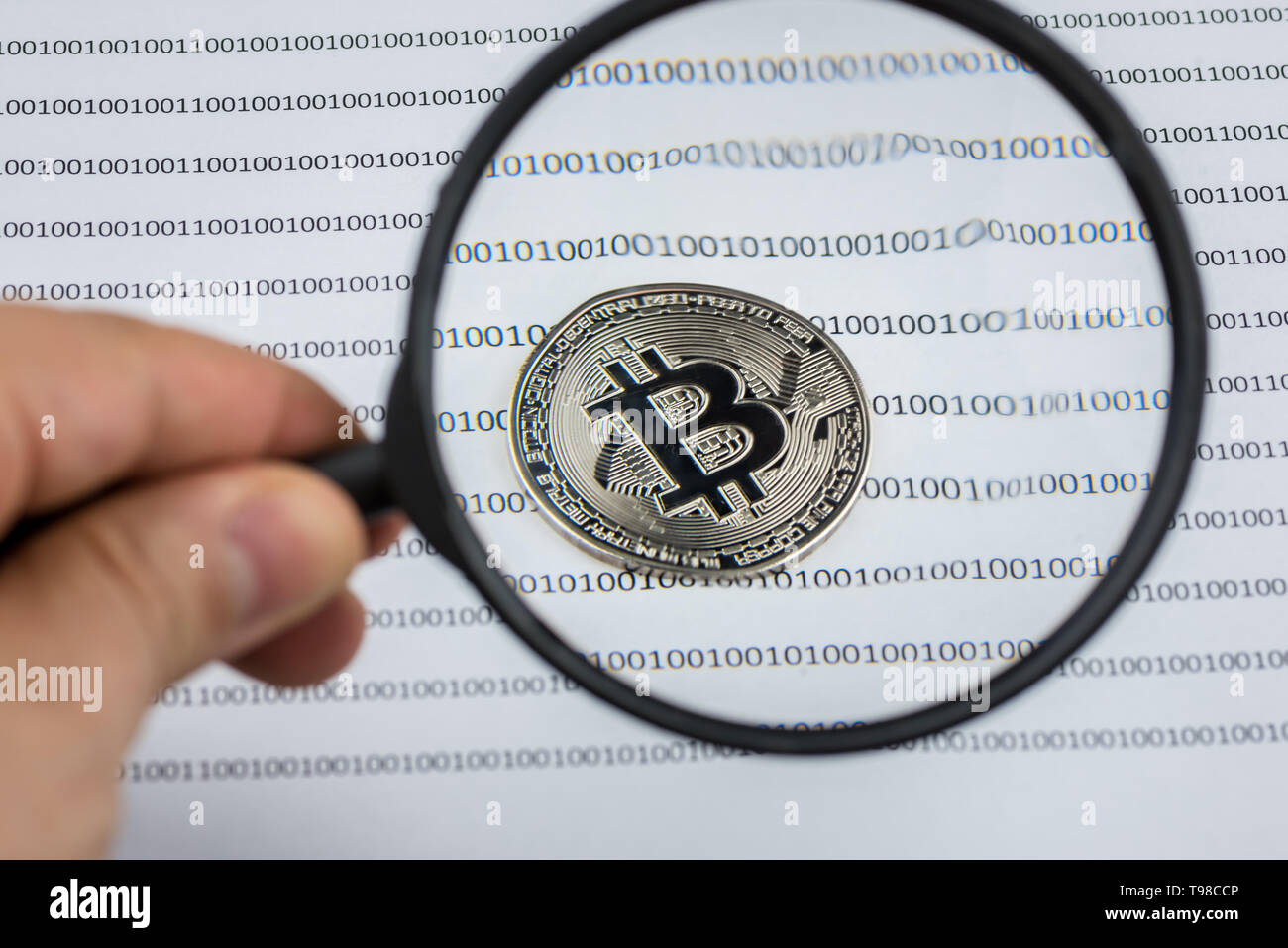 Man hand holds magnifying glass over bitcoin, cryptocurrency physical coin on paper with binary system of zeros and ones.Virtual cryptocurrency concep - Stock Image