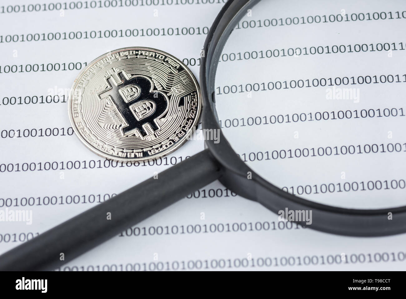 Magnifying glass over bitcoin, cryptocurrency physical coin on paper with binary system of zeros and ones.Virtual cryptocurrency concept.Concept image Stock Photo