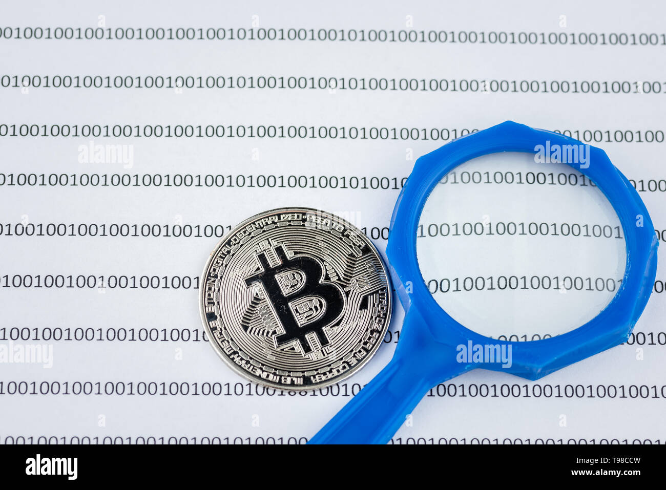 Magnifying glass over bitcoin, cryptocurrency physical coin on paper with binary system of zeros and ones.Virtual cryptocurrency concept.Concept image - Stock Image