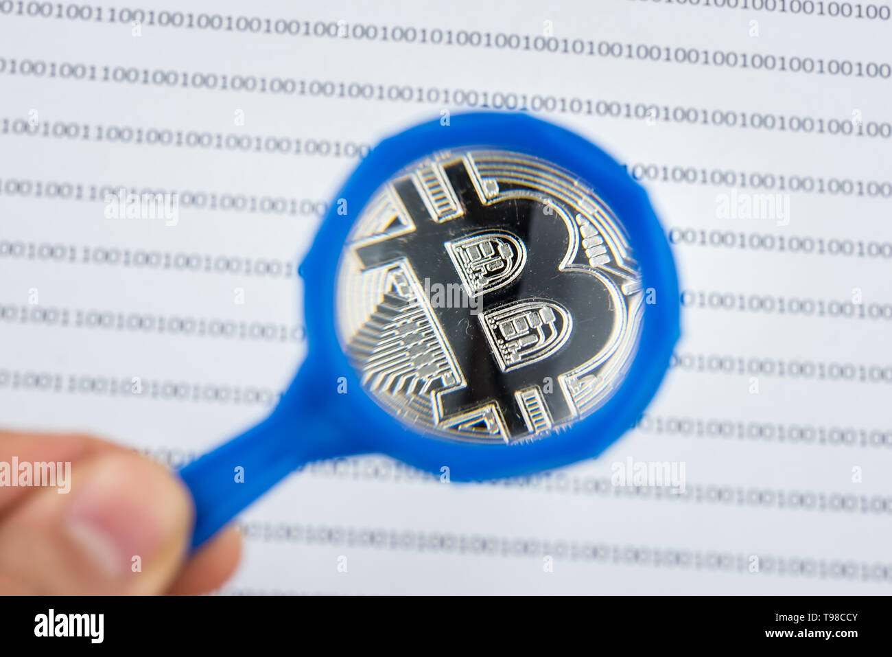 Man hand holds magnifying glass over bitcoin, cryptocurrency physical coin on paper with binary system of zeros and ones.Virtual cryptocurrency concep Stock Photo
