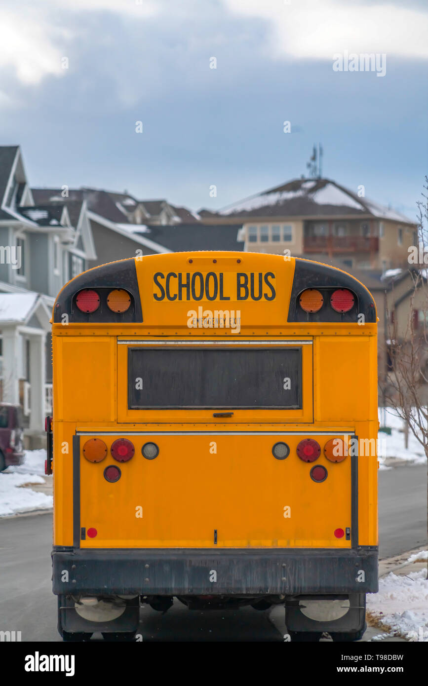 Rear of a yellow school bus against snowy homes and cloudy sky in winter - Stock Image