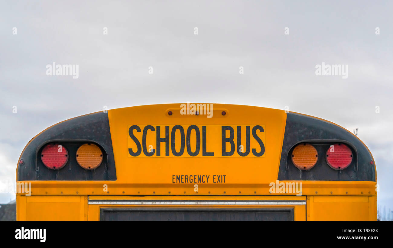 Clear Panorama Rear of a yellow school bus with signal lights and emergency exit window - Stock Image