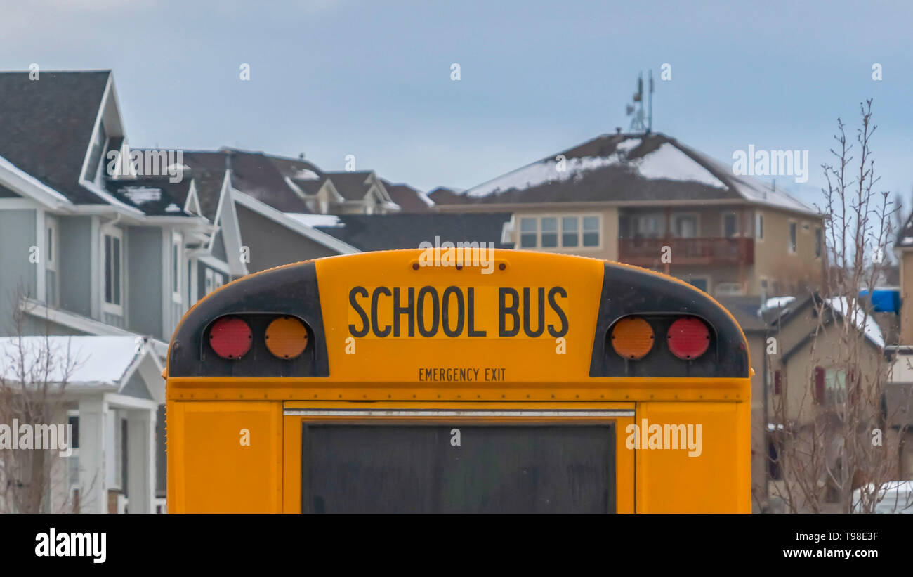 Clear Panorama Rear view of a yellow school bus with a window and several signal lights - Stock Image