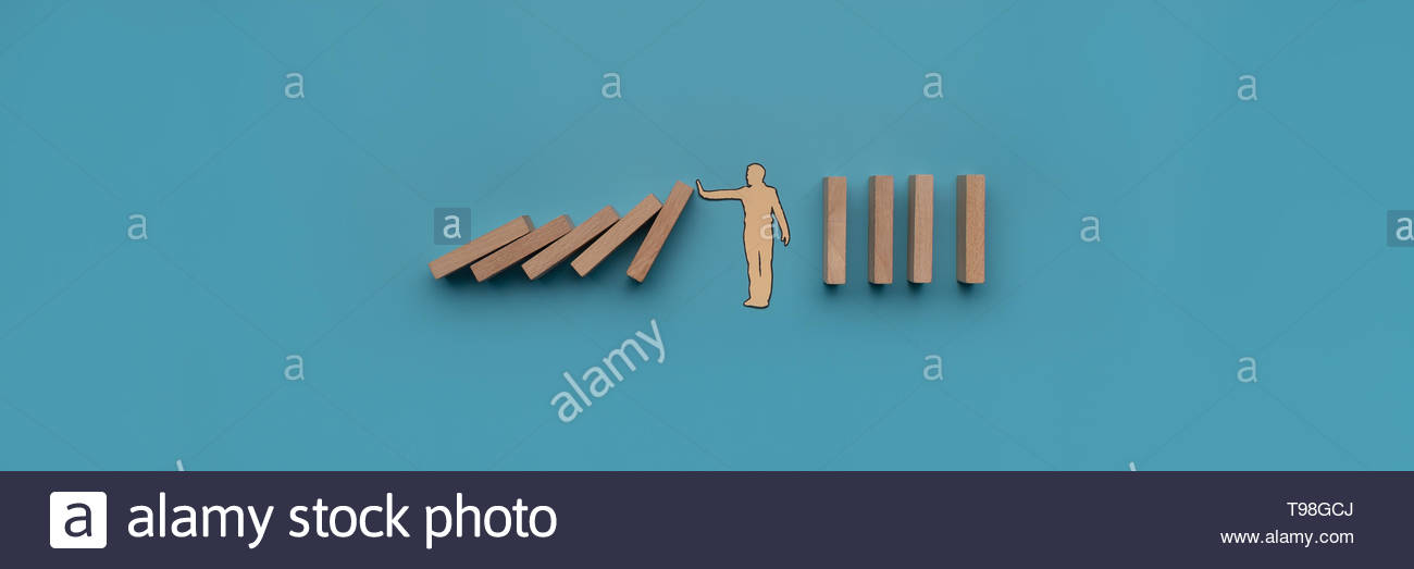 Paper cut silhouette of a paper man stopping dominos from falling. Wide view image over blue background. - Stock Image