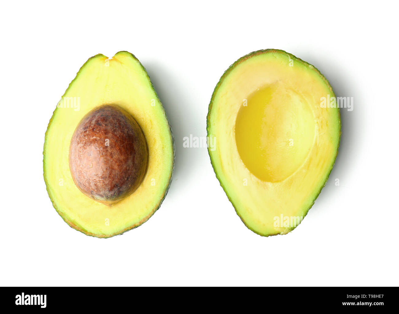 Halves of ripe fresh avocado on white background - Stock Image