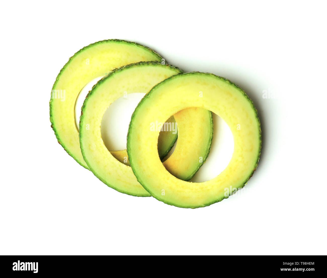 Slices of ripe fresh avocado on white background - Stock Image