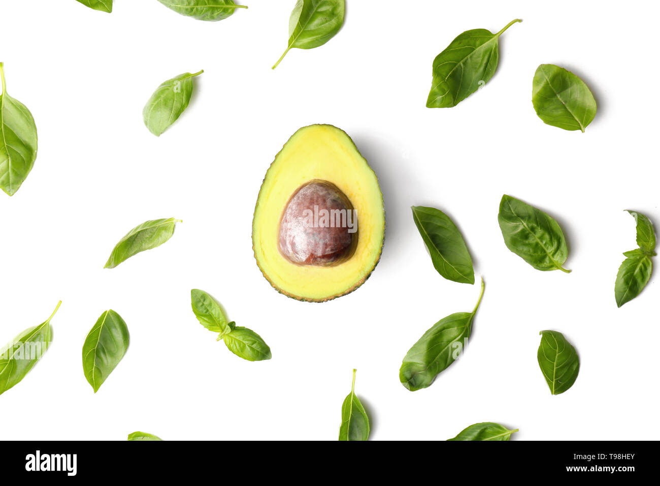 Half of ripe avocado and basil leaves on white background - Stock Image
