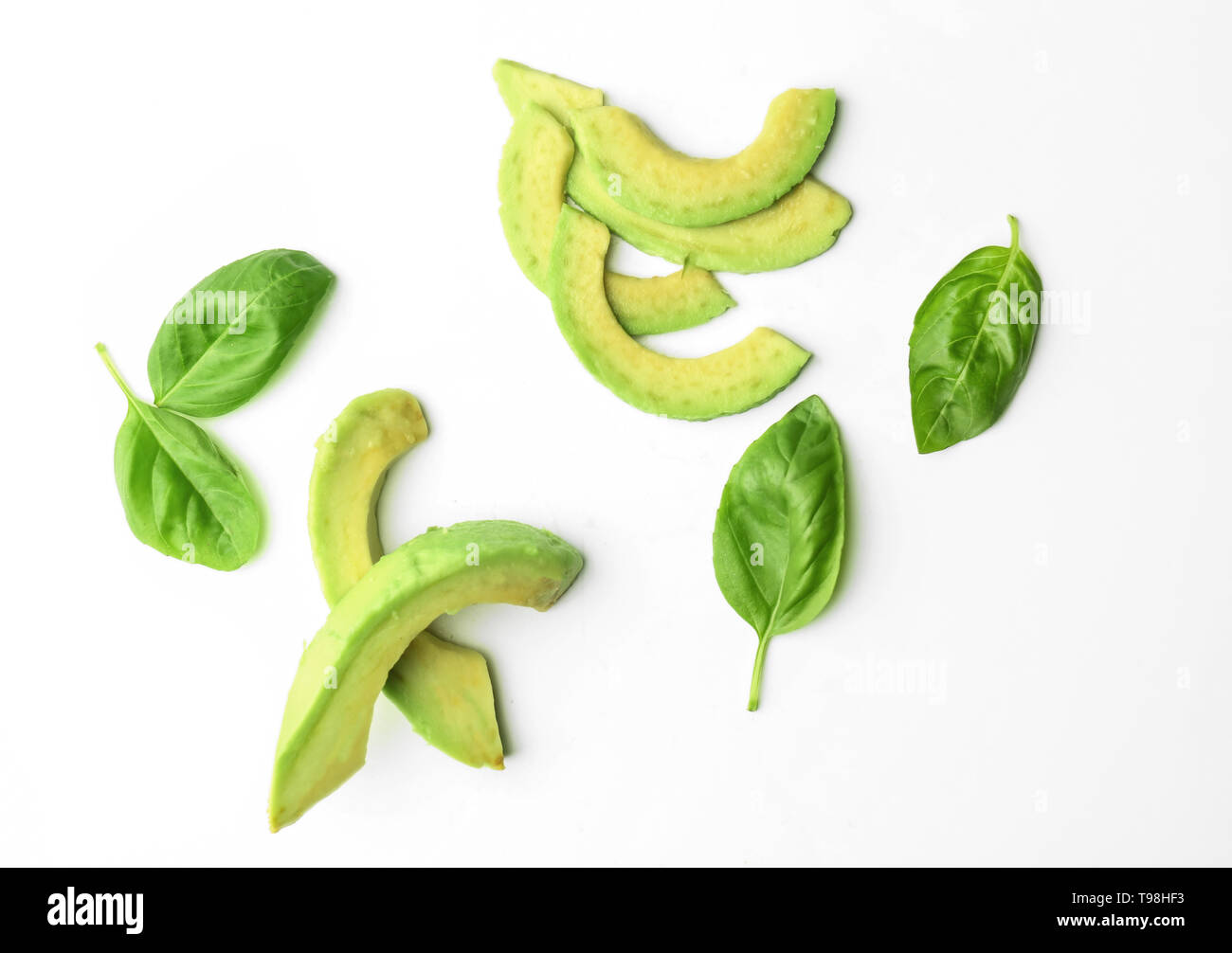 Slices of avocado and basil leaves on white background - Stock Image