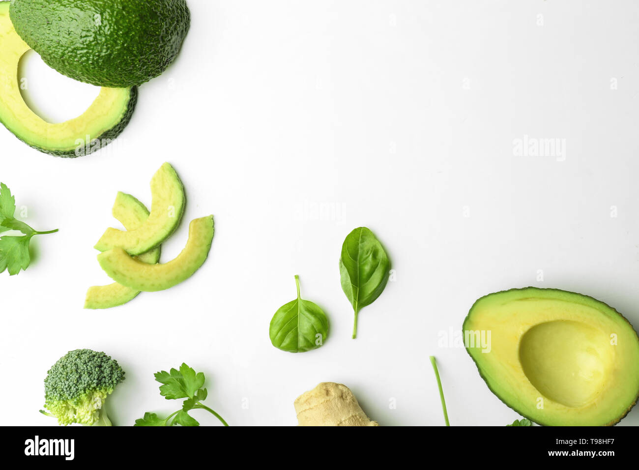 Composition with cut avocado on white background - Stock Image