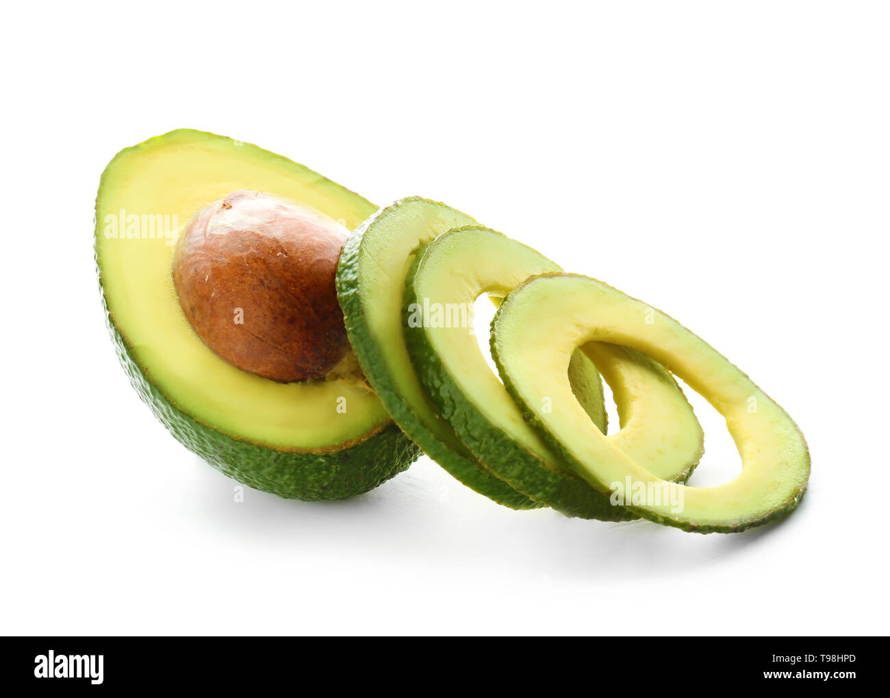 Cut ripe avocado on white background - Stock Image