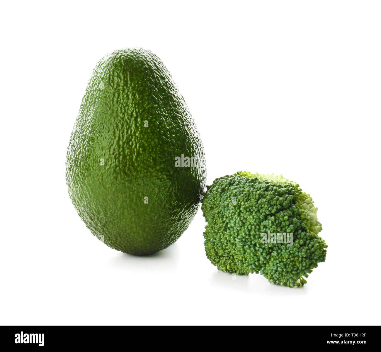 Ripe avocado and broccoli on white background - Stock Image