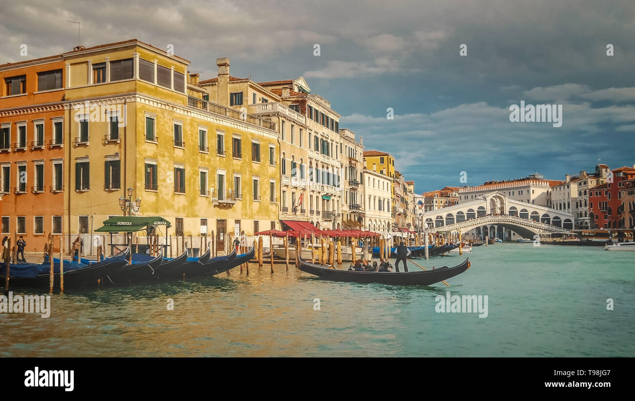 Gondola Along Grand Canal and Rialto Bridge in Venice, Italy - Stock Image