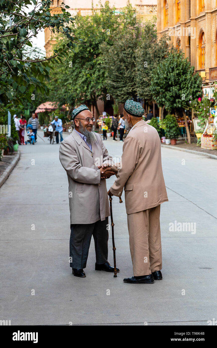 Aug 2017, Kashgar, Xinjiang, China: two local uighur men warmly shaking hands in the streets of Kashgar Old Town, a major tourist spot along the Silk  - Stock Image