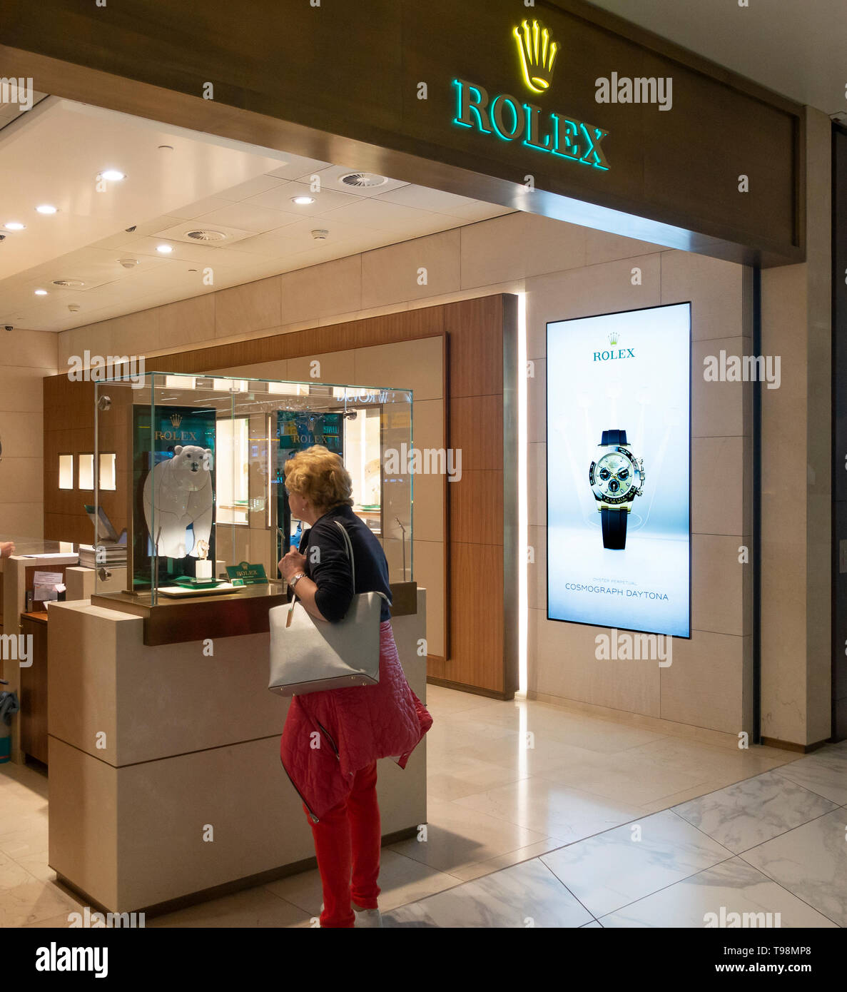 A woman passenger looks at a watch in a display in the Rolex retail outlet in Schiphol Airport, Amsterdam, the Netherlands. - Stock Image