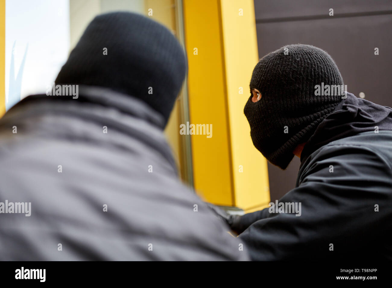 Two burglars quietly explore a house through a window for a burglary - Stock Image